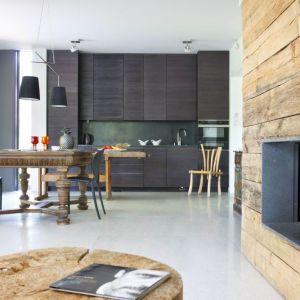 Wnętrza są eklektyczne i niepowtarzalne. Bazę, tak jak na zewnątrz, stanowią naturalne materiały – jasny kamień na podłodze, kamień ogrodowy na ścianach w łazience, surowe szalunkowe deski na suficie czy obudowa kominka z belek, które zostały po budowie tężni. Projekt i zdjęcia: Kulczynski Architekt