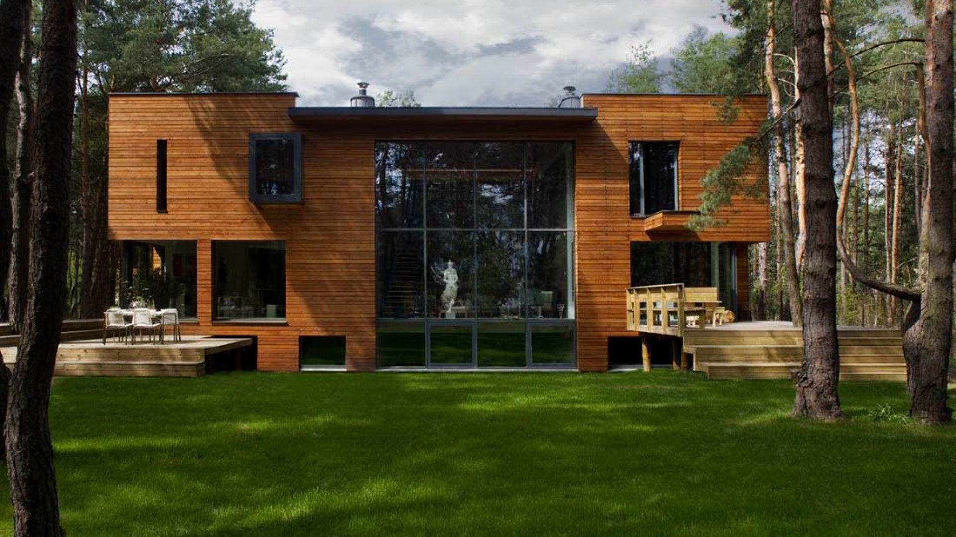 Dom został wybudowany na malowniczej działce pod Warszawą. Elewacja pokryta jest modrzewiowymi deskami oraz bazaltem powulkanicznym. Projekt i zdjęcia: Kulczynski Architekt