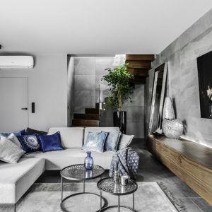 W tym salonie królują szarości. Szara jest nie tylko sofa, ale także ściany, podłoga oraz dywan. Projekt Agnieszka Morawiec. Fot. Dekorialove