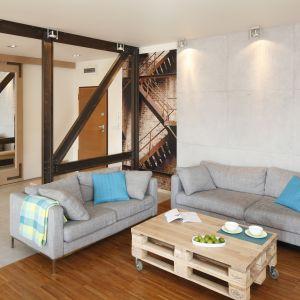 Jasne kanapy doskonale pasują do nowoczesnego salonu urządzonego również w jasnych kolorach. Nóżki dodają im lekkości, a turkusowe dodatki pięknie ożywiają. Projekt: Marta Kruk. Fot. Bartosz Jarosz