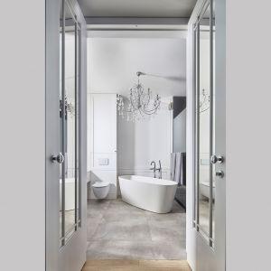 W łazience z kolei kryształowy żyrandol występuje ramię w ramię z… betonową podłogą. Te kontrasty nadają ton całej aranżacji. Projekt: Anna Koszela. Fot. Budzik Studio