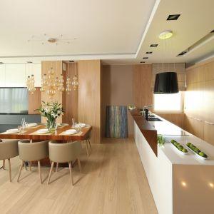 W kuchni wykorzystano jego dwa rodzaje: dąb bielony (obecny na podłogach w postaci olejowanych desek, zabudowie kuchennej i części ścian w strefie dziennej) oraz orzech amerykański (zdobiący fragmenty ścian). Projekt: Laura Sulzik. Fot. Bartosz Jarosz