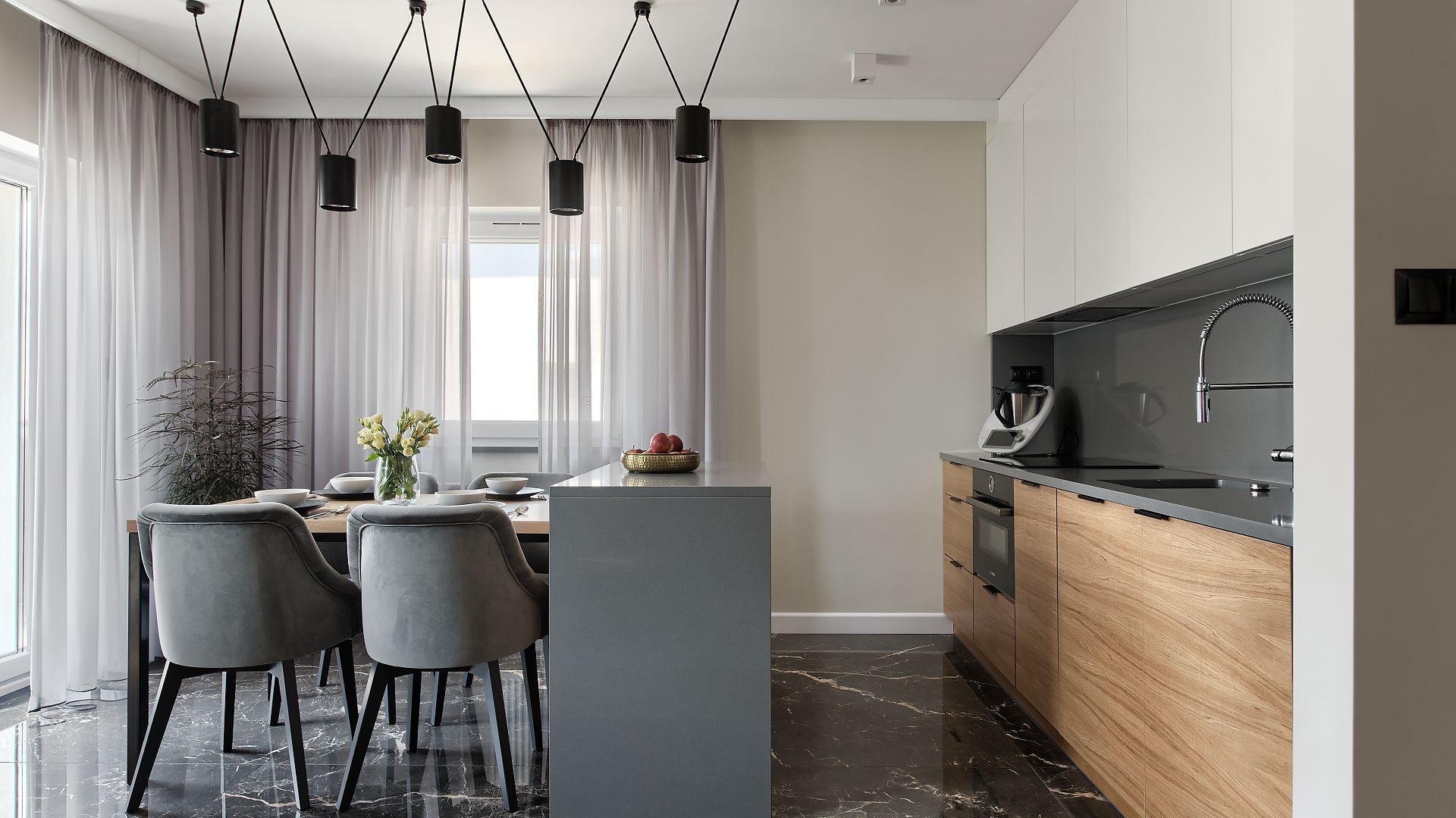 W kuchni znajduje się wyspa, przy której ustawiono stół i krzesła, pełniące rolę wygodnej jadalni. Projekt: pracownia M-Studio. Fot. Radek Słowik
