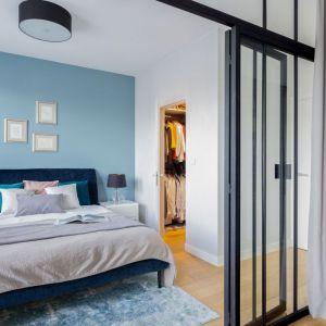 Niebieska ściana za łóżkiem doskonale pasuje do białych ścian, dywanu oraz łóżka w kolorze granatu. Projekt: Katarzyna Rohde. Fot. Marta Behling, Pion Poziom