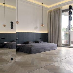 Naprzeciwko łóżka ustawiono dużą szafę z przeszklonymi drzwiami, które optycznie powiększają wnętrze. Projekt: Aga Kobus i Grzegorz Goworek, Studio. O