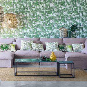 Aranżacja salonu w stylu jungle. Tapeta z liśćmi palmowymi i poduszki z podobnym wzorem oraz modne lampy z plecionki w stylu boho. Podobne lampy np. HK Living - ok. 2200 zł. Fot. Nedgis