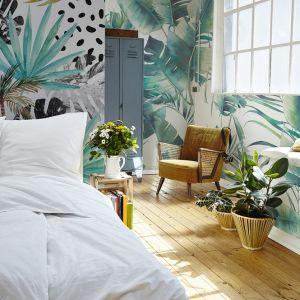 Aranżacja sypialni w stylu urban jungle. Tak mocne desenie najlepiej wyglądają na tle naturalnej jasnej podłogi i bieli. Podobny wzór tapety możemy dostać jako tapetę winylową lub samoprzylepną. Winylowa - od 79 zł, samoprzylepna - od 149 zł, Pixers