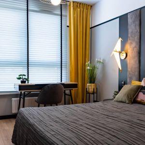 Żółte dodatki doskonale ocieplają szarą kolorystykę ścian oraz zagłówka. Projekt: DG Studio Donata Gadalska. Fot. Jacek Fabiszewski
