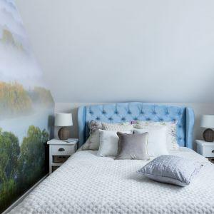 W sypialni pięknie prezentuje się niebieski łóżko z pikowanym zagłówkiem. Podobnie jak fototapeta przedstawiające Górę Strękową u zbiegu Biebrzy i Narwi. Projekt: Justyna Mojżyk, poliFORMA. Fot. Monika Filipiuk-Obałek
