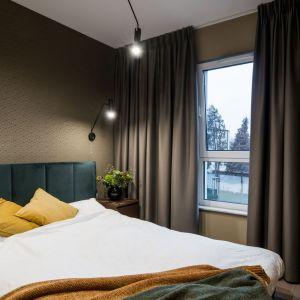 Ciemna kolorystyka zastosowana w sypialni nadaje jej przytulności. Brązy idealnie pasują do butelkowej zieleni oraz poduszek w żółtym kolorze. Projekt i zdjęcia: Pracownia KODO Projekty i Realizacje Wnętrz
