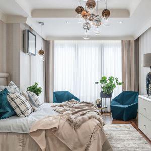 Sypialnia to królestwo ciepłych beży, przybrudzonych bieli i delikatnych szarości. Wnętrze ożywiają jednak dodatki w niebieskim kolorze. Projekt: Joanna Safranow. Fot. Fotomohito