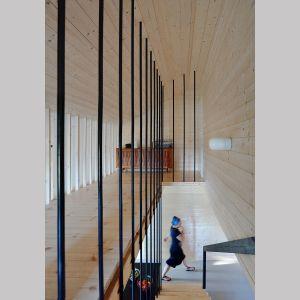 Centralnie umieszczone schody oddzielają salon od przedpokoju i pomieszczeń zamkniętych – głównej sypialni, łazienki i toalety. Projekt i zdjęcia: architekt Grzegorz Layer