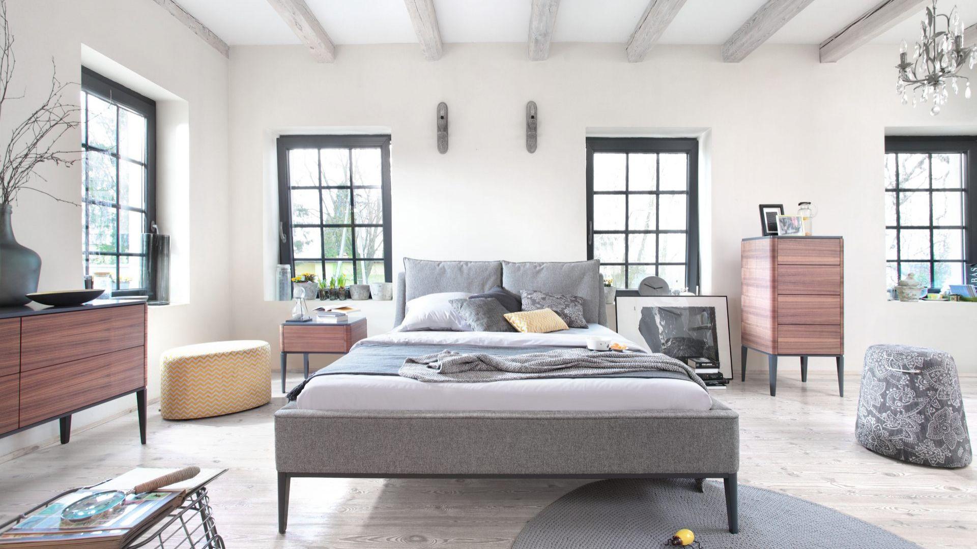 Łóżko Essence, 160 lub 180 cm, tapicerka: tkanina obiciowa. Luźne poduszki, mocowane do zagłowia na rzepy. Nogi i rama drewno bukowe lub dębowe. Mebel sprawia wrażenie wizualnie lekkiego, dzięki smukłym, drewnianym nóżkom i dekoracyjnej listwie, a jego forma ułatwia sprzątanie w sypialni. Od 7100 zł, Swarzędz Home
