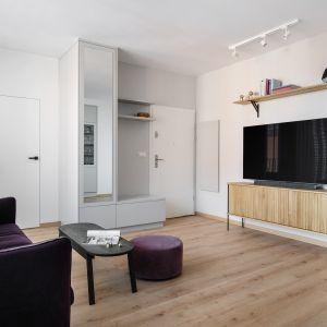 Salon z bakłażanową sofą jest miejscem wypoczynku i relaksu. Może z niego wyjść na dość spory balkon z meblami wypoczynkowymi. Projekt: Monika Wierzba-Krygiel. Fot. Hania Połczyńska