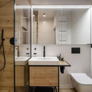 Małą łazienkę o dębowo-białej kolorystyce uzupełnia mocny akcent w postaci płytek z roślinnym wzorem pod prysznicem. Projekt: Monika Wierzba-Krygiel. Fot. Hania Połczyńska