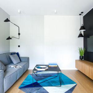 W salonie, monochromatyczność wnętrza przełamano akcentami w kolorze granatowym oraz bardzo oryginalnym dywanem ze skróty o nieregularnym kształcie. Projekt: Sandra Maculewicz. Fot. Łukasz Pepol