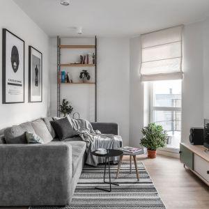 Kolorystyka dywanu doskonale pasuje do szarej kanapy, jasnych ściana i drewnianej podłogi. Podobnie jak bardzo ciekawy wzór dywanu. Projekt: Raca Architekci. Fot. Fotomohito