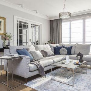 Do pięknego salonu urządzonego w stylu Hampton doskonale pasuje jasny dywan. Ładnie prezentuje się na tle drewnianej podłogi. Projekt: Decoroom. Fot. Pion Poziom