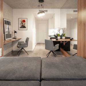 Dwuosobowe łóżko, które zamienia się w kanapę, składane biurko i duże lustro optycznie powiększające wnętrze. pokazowy we Wrocławiu o powierzchni 18,5 m2. fot. BY MADE