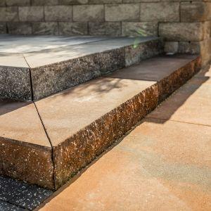 Polbruk Grando występuje w dwóch fakturach: łamanej i gładkiej. Ta pierwsza przypomina ciosany kamień, a druga zbliżona jest wyglądem do granitu. Na zdjęciu: stopień Grando w kolorze hawaii mokka. Fot. Polbruk
