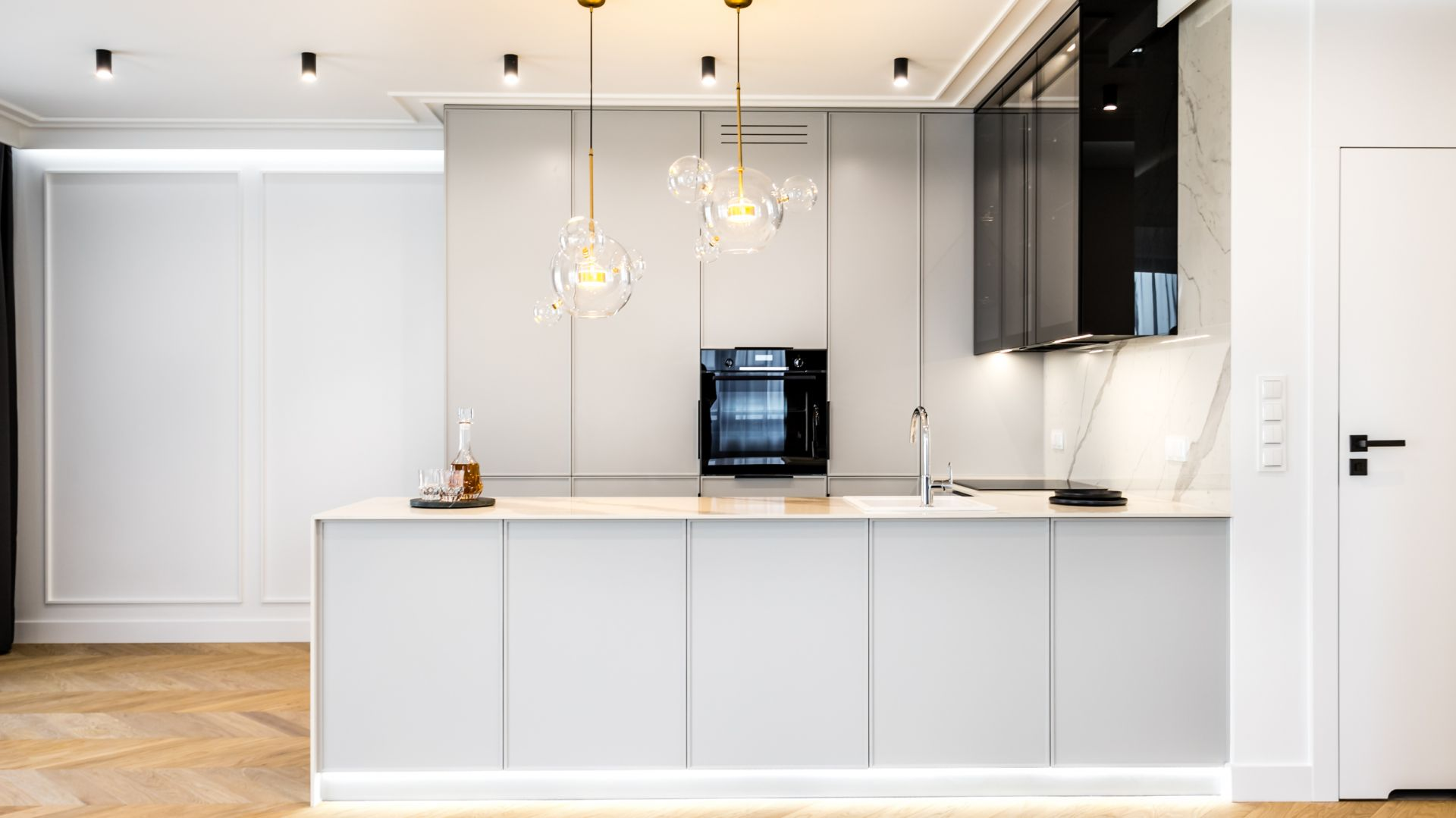 Kuchnia otwarta na salon zaprojektowana w jasnych kolorach. Projekt: Anna Milczarek, Moovin Group