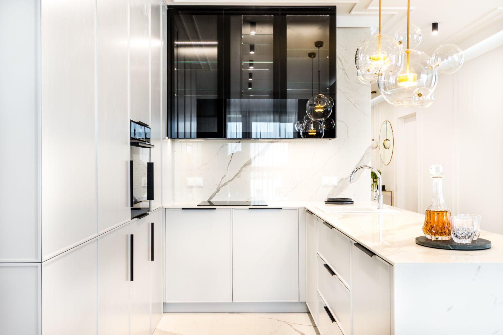 Biała zabudowa kuchenna i odbijające światło okładziny ścienne. Projekt: Anna Milczarek, Moovin Group
