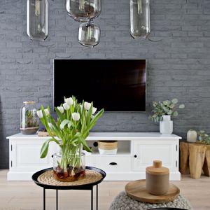 Stylowa biała komoda pod telewizorem i szara cegła na ścianie z tv. Projekt wnętrza: SHOKO design