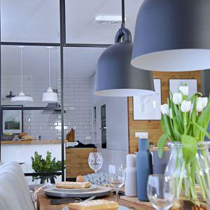 Jadalnia urządzona w inspirowanym naturą stylu, nad drewnianym solidnym stołem wiszą piękne szare lampy. Projekt wnętrza: SHOKO design