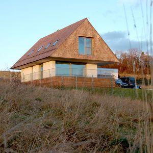 Na dachu, ścianach szczytowych i ogrodzeniu frontowym architekcie zastosowali gont z cedru kanadyjskiego. Projekt domu: Jarek Krysiak, Barbara Borowik-Krysiak, Doomo studio architektoniczne. Fot. Piotr Lipecki