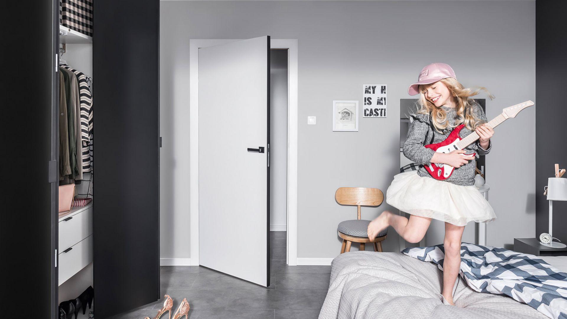 Krawędź prostych, białych drzwi Modus, która zazwyczaj jest ukryta, wykończona została materiałem przypominającym naturalną sklejkę lub okleiną w pięknym antracytowym kolorze. Cena: od ok. 400 zł. Fot. Vox
