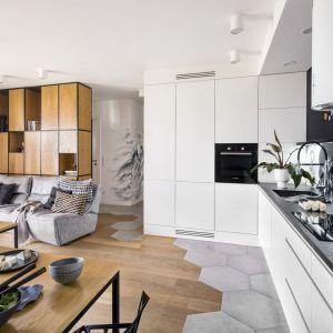 Czarny granitowy blat i pomalowana czarną, magnetyczną farbą ściana w kuchni tworzą mocny kontrast z minimalistycznymi białymi szafkami i nadają sznyt całości. Projekt: Zuzanna Kuc, ZU projektuje. Fot. Łukasz Zandecki
