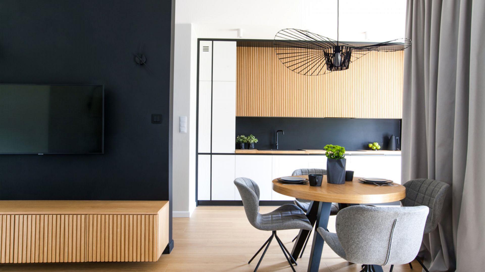 Ścianę nad kuchennym blatem zdobi czarne, matowe, piaskowane szkło. Jest ono znacznie łatwiejsze w czyszczeniu niż popularny lacobel. Projekt: Sandra Maculewicz. Fot. Łukasz Pepol