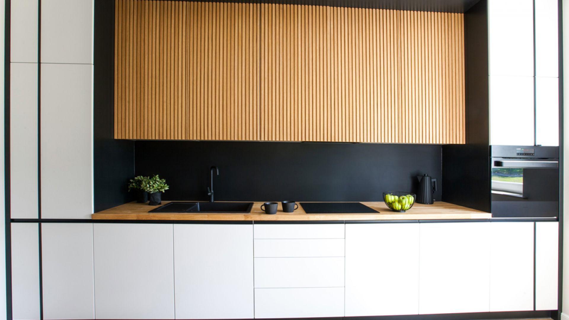 Czarne szkło nad kuchennych blatem oraz białą zabudowę piękne ocieplają frezy na drewnianych szafkach wiszących.  Projekt: Sandra Maculewicz. Fot. Łukasz Pepol