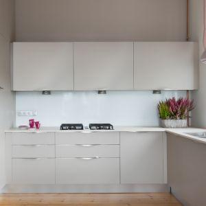 Kuchnia jest ultra funkcjonalna i minimalistyczna. Fronty z delikatną fakturą w kolorze taupe współgrają z gamą beżowo-różowych barw zasłon okiennych. Projekt: Marta Kodrzycka, Marta Wróbel. Fot. Magdalena Łojewska