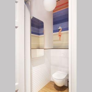Mała łazienka również jest inspirowana klimatem sopockim, stąd pojawia się tu okładzina ścienna z motywem plaży, morza i lata, poniżej białe płytki w pasy nawiązują do charakterystycznego dla Sopotu i mola deskowania malowanego na biało. Projekt: Marta Kodrzycka, Marta Wróbel. Fot. Magdalena Łojewska