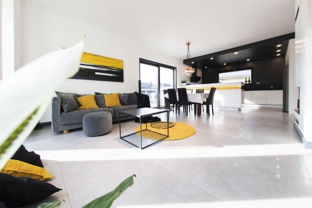 Nowoczesne wnętrze jest jasne, przestronne i urządzone bardzo wygodnie. Drewno w nieoczywistym miodowym odcieniu pięknie łączy się z bielą, czernią i szarościami. Całość ożywają zaś żółte dodatki.