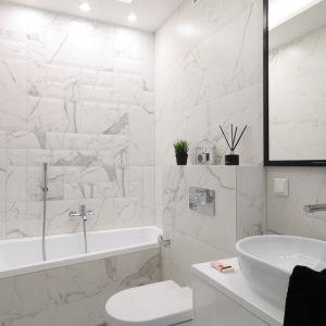 Płytki z kamiennym wzorem sprawdzą się też w małej łazience w bloku. Na zdjęciu niewielka łazienka z wanną. Projekt Katarzyna Mikulska-Sękalska. fot. Bartosz Jarosz