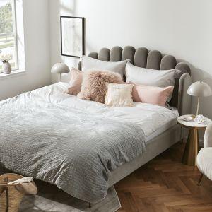 Tapicerowane łóżko z miękkim nagłówkiem i przytulne narzuty i poduszki to sposób na wypoczynek w sypialni. Fot. WestwingNow