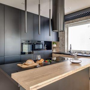 Ciemne szare meble z matowymi frontami sprawiają, że kuchnia jest nowoczesna, ale i elegancka. Projekt: Marta Kilan, Anna Kapinos, Tomasz Słomka. Fot. Radosław Sobik