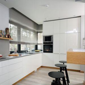 Zestawienie szarych ścian i blatu z prostymi, białym meblami oraz drewnianą podłoga dało efekt lekkości w kuchni. Projekt: Laura Sulzik. Fot. Bartosz Jarosz