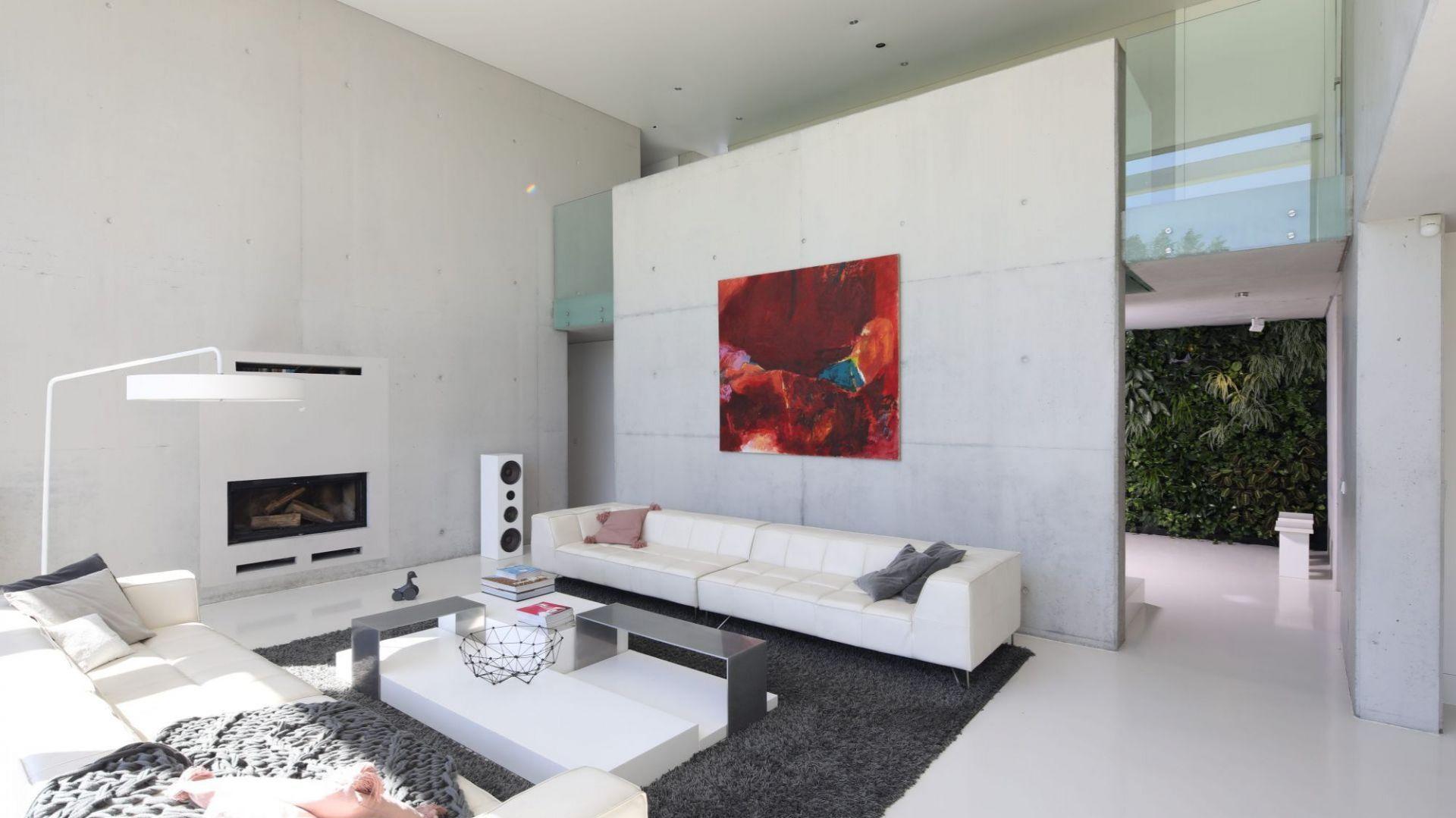 """W tym salonie beton jest jednocześnie elementem konstrukcyjnym i dekoracyjnym. Architekci i właściciele zarazem cenią sobie """"szczerość"""" tego materiału, pozwalającego wykonać solidną konstrukcję o dużej rozpiętości, która nie jest przytłaczająca i przy tym wspaniale się prezentuje. Projekt: Hanna i Seweryn Nogalscy. Fot. Bartosz Jarosz"""