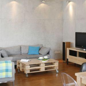 Betonowe płyty zdobią dwie główne ściany w salonie urządzonym w stylu loft. Projekt: Marta Kruk. Fot. Bartosz Jarosz.