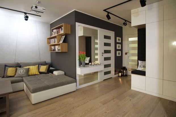 Jakie efekty przynosi wnętrze pełne bieli, drewna i głębokiej szarości? W połączeniu z prostymi, geometrycznymi formami – efekt nowoczesnego, nieskomplikowanego wzornictwa. Autorkami projektu są architektki z 4Rooms Studio, które aranżację wn