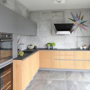 W tej kuchni szare są zarówno meble, jak również podłoga i ściany. Całość doskonale ociepla drewno. Ciekawym akcentem dekoracyjnym są z kolei kolorowe gwiazdy na ścianie. Projekt: Magdalena Lechmann. Fot. Bartosz Jarosz