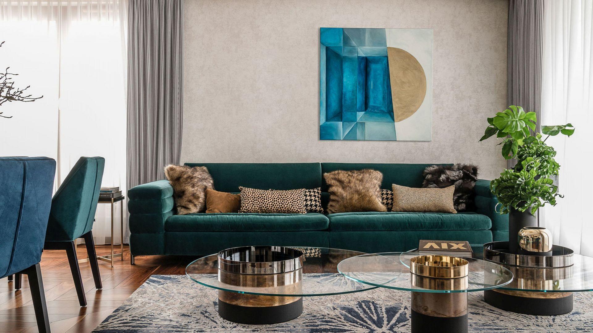 Odważna kolorystyka usadowiła się tu na miękkich, welurowych obiciach sofy. Butelkowa zieleń w zestawie z piaskową tapetą tworzą spójną stylistycznie przestrzeń. Projekt Joanna Safranow. Fot. Fotomohito