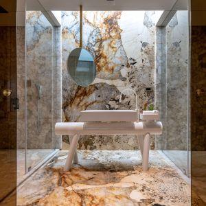 Łazienka z pięknym kamieniem na ścianach i podłodze. Projekt: NA Architects. Zdjęcia: Boca do Lobo
