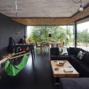 W części dziennej dominuje czerń ścian, pozostawiono tu nawet nietynkowane betonowe stropy. Uzupełniają ją białe i zielone dodatki oraz drewniane elementy z litego jesionu. Projekt:  Robert Skitek, pracownia RS+. Fot. Tomasz Zakrzewski