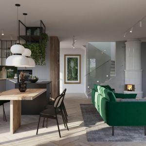 W centralnym punkcie salonu ustawiono rozłożysty, choć dzięki smukłym nóżkom bardzo zgrabny, narożnik w przepięknej barwie nasyconej zieleni, która wybija się na tle szarości ściany oraz dywanu. Mebel idealnie współgra z pozostałymi elementami, bo całe mieszkanie zyskało oprawę szlachetnej palety kolorystycznej, jaką tworzą czerń i biel, butelkowa zieleń oraz gołębia szarość, ocieplone gdzieniegdzie piaskowym beżem. Projekt i wizualizacje: Agata Kasprzyk-Olszewska