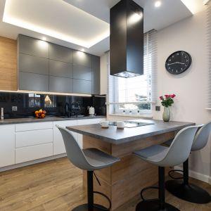 Szarości połączono w tej kuchni z bielą, drewnem i elegancką czernią Projekt: Anna Kamińska, Fuxja Studio Projektowe. Fot. Alla Boroń