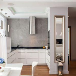 Niedużą kuchnię urządzono w bielach i szarościach, które ociepla drewniana podłoga. Na tle szarych płytek pięknie został wyeksponowany okap. Projekt: Arkadiusz Grzędzicki. Fot. Panadam.pl